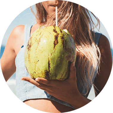 The sporty woman drinks coconut water